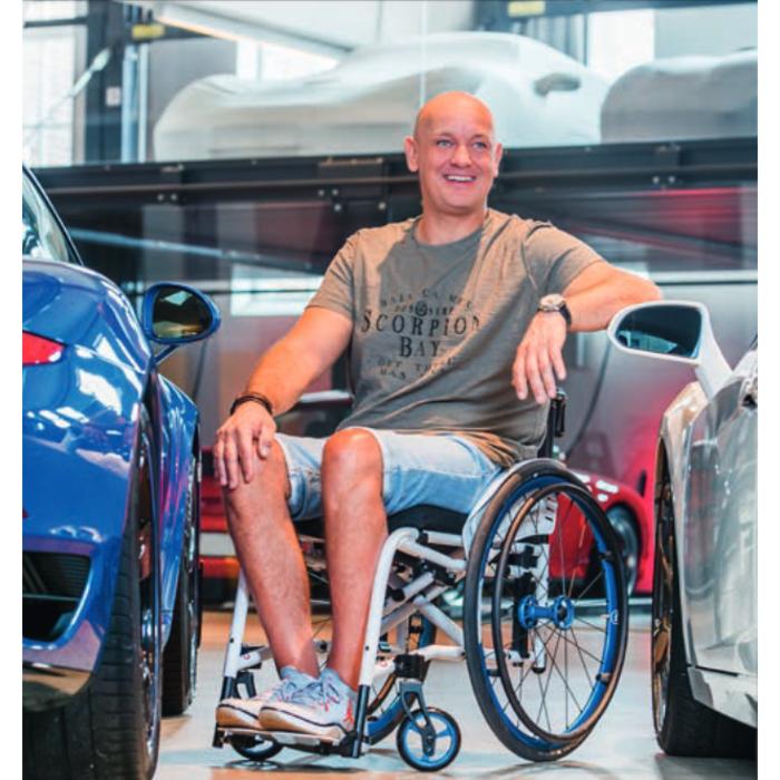 Ein weißer mittelalter Mann sitzt im Rollstuhl in einem Autohaus.