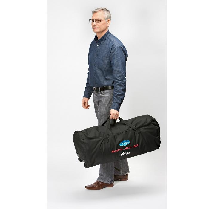 Ein älterer Mann trägt eine schwarze Tasche. Er hat ein blaues Hemd und eine graue Hose an. Er trägt eine Brille.