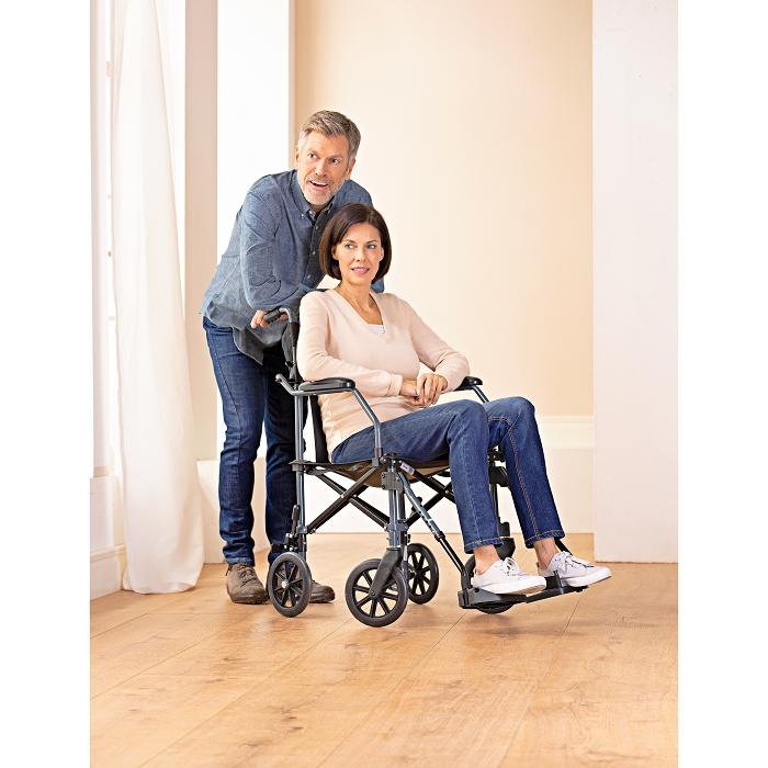 Eine Frau sitzt in einem Rollstuhl in einem Zimmer. Hinter ihr steht ein Mann mit Brille, der sich mit den Armen am Rollstuhl anlehnt.