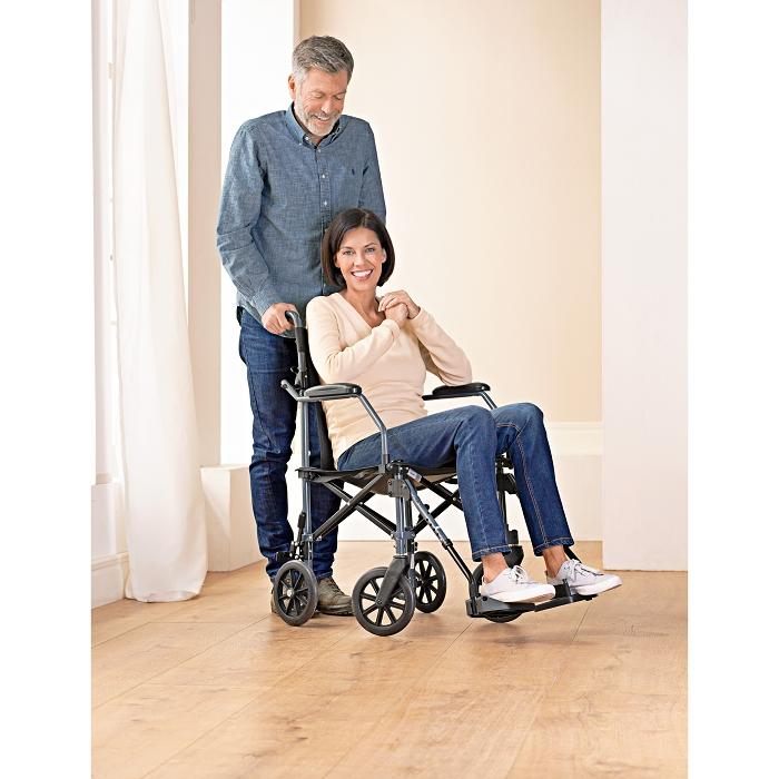 Eine Frau sitzt in einem Rollstuhl in einem Zimmer. Hinter ihr steht ein Mann mit Brille und hält sich an den Griffen des Stuhls fest.