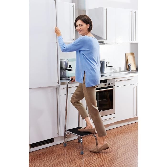 Eine ätere Frau steigt in einer Küche auf eine Trittstufe mit Haltegriff. Der Boden ist holzfarben, die Frau hat ein blaues Oberteil und kurze, braune Haare. Sie guckt in die Kamera.