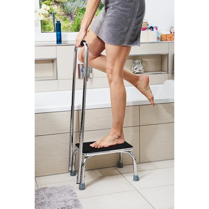 Ausschnitt einer Frau die auf eine Trittstufe mit Haltegriff steigt. Sie ist abei in eine Badewanne zu steigen und ist Barfuß und hat ein Handtuch um die Hüfte.