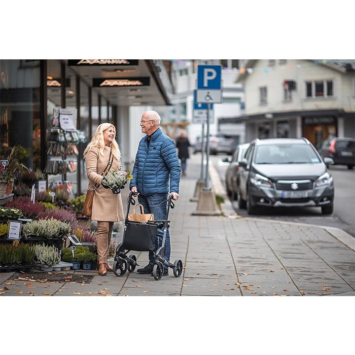 Zu sehen ist ein älteres Paar vor einem Blumenladen. Die Frau hat Blumen in der Hand und der Mann stützt sich auf einem grau-schwarzen Rollator ab.