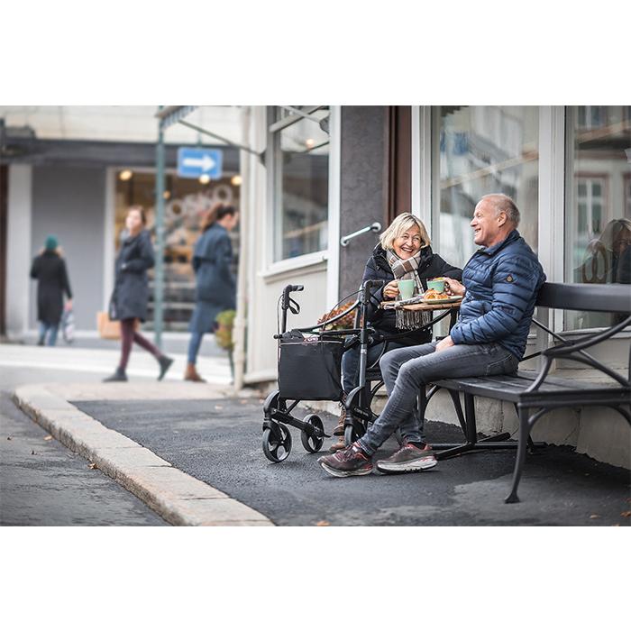 Ein älteres Pärchen sitzt an einem Tisch draußen und isst. Beide lachen. Vor dem Tisch ist ein schwarzer Rollator.