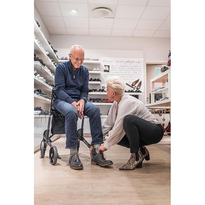 Ein älterer Mann in einem Schuhgeschäft. Er sitzt in seinem Rollator und eine Frau hilft ihm beim Schuhe anziehen.