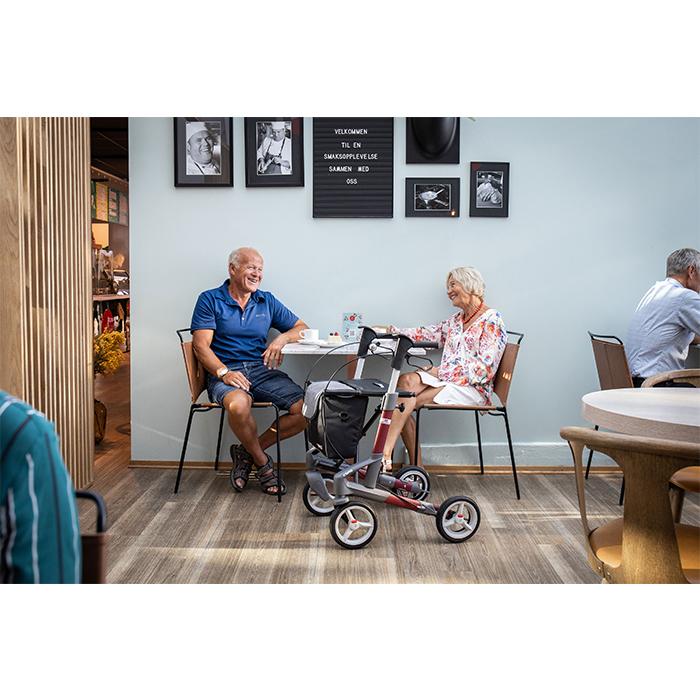 Ein altes Ehepaar sitzt in einem Café an einem Tisch. Beide lachen. Vor dem Tisch steht ein weinroter Rollator mit schwarzer Tasche.