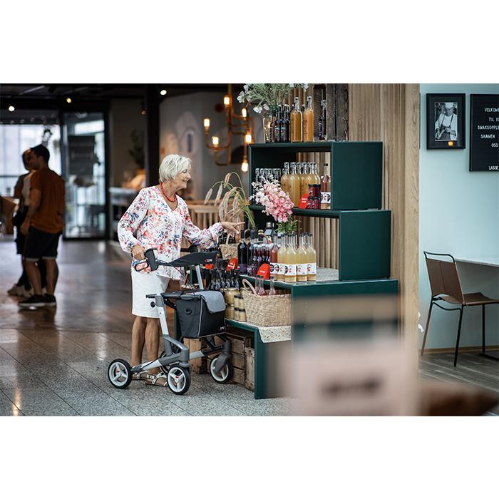 Eine ältere Frau steht vor einem Getränkeregal und greift nach einer Flasche. Gestützt wird sie von einem grau-weißen Rollator.