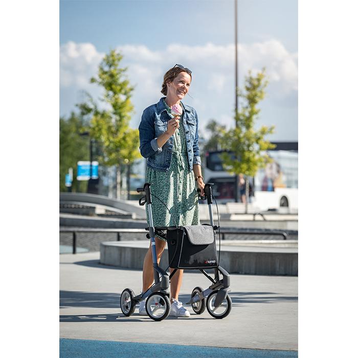 Eine jüngere Frau in einem Kleid und Jeansjacke steht in einem Park und isst ein Eis. Mit der rechten Hand stützt sie sich auf einem grauen Rollator ab.