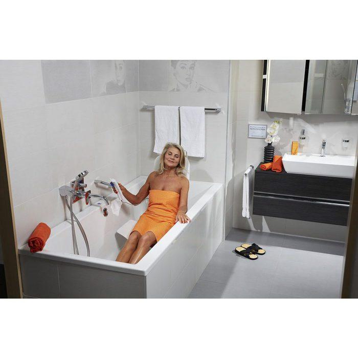 Eine Frau in einem gelben Handtuch sitz in einer leeren Badwanne