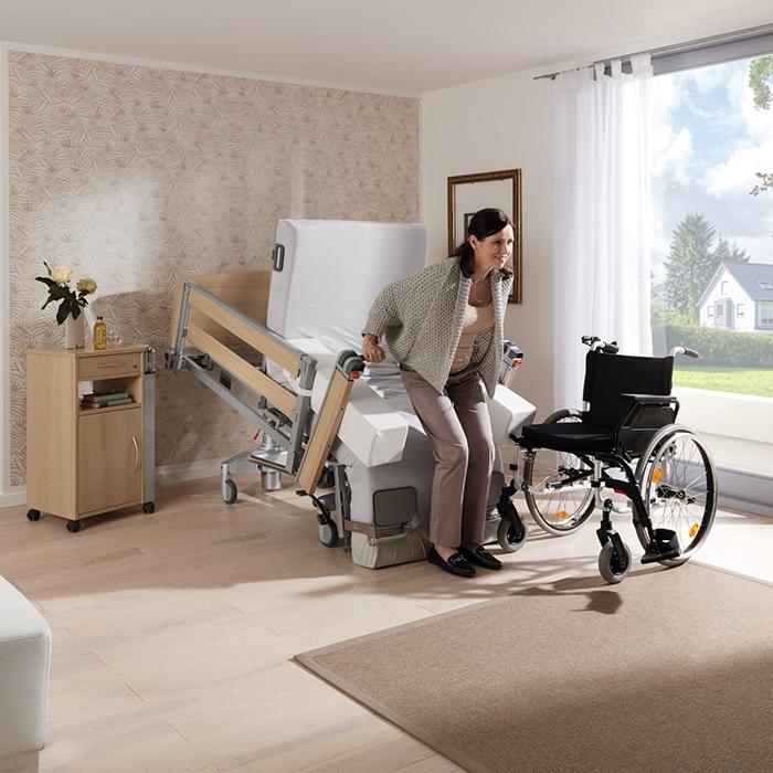 Frau steht aus Pflegebett mit Aufstehhilfe auf.