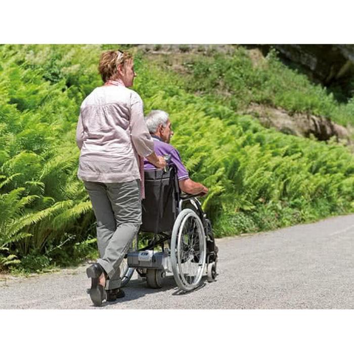 Eine Frau schiebt einen Mann im Rollstuhl einen steilen Weg hoch. Sie laufen auf einem Weg der in der Natur liegt.