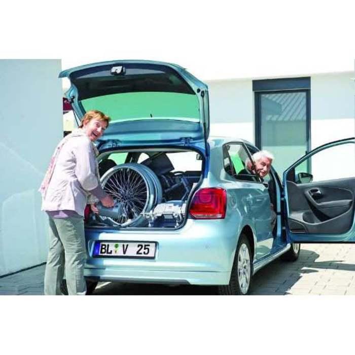 Eine Person verstaut gerade einen Rollstuhl in einem kleinen VW Polo. Das Auto hat eine hellblaue Farbe.