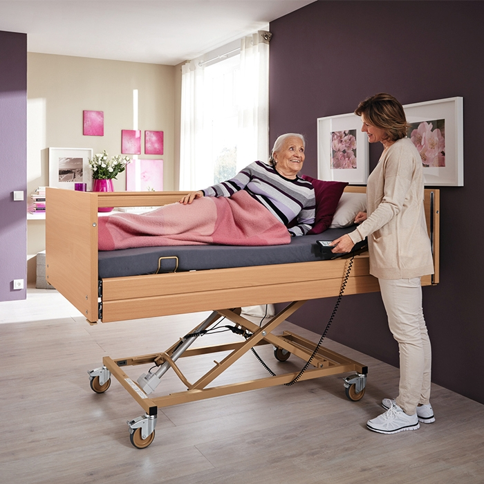 Frau liegt in Pflegebett, Pflegerin steht daneben und bedient den Handschalter.