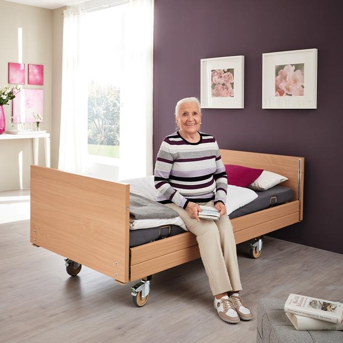 Frau sitzt auf dem Rand eines Pflegebettes.